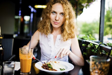 Woman Eating Healthy Salad in a restaurant outdoor terrace